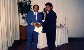 Rajan Sachdev receiving award from Executive Director Modi GBC during an awards night in Singapore.